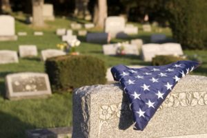 A folded US flag on a grave.
