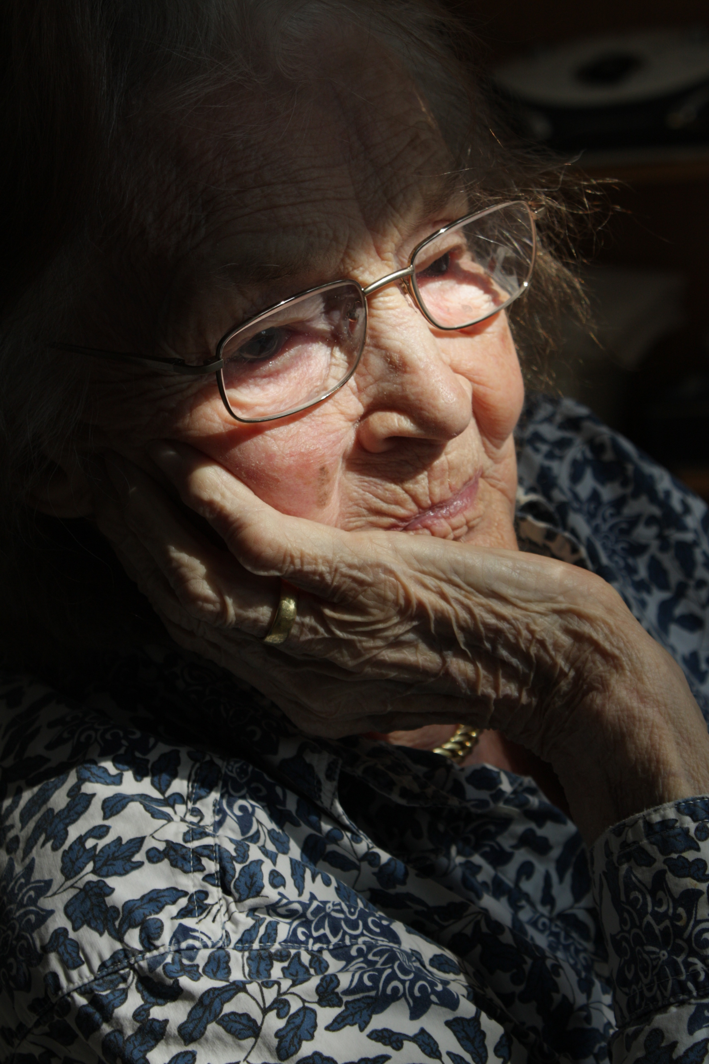 Elderly woman sitting in a ray of light.