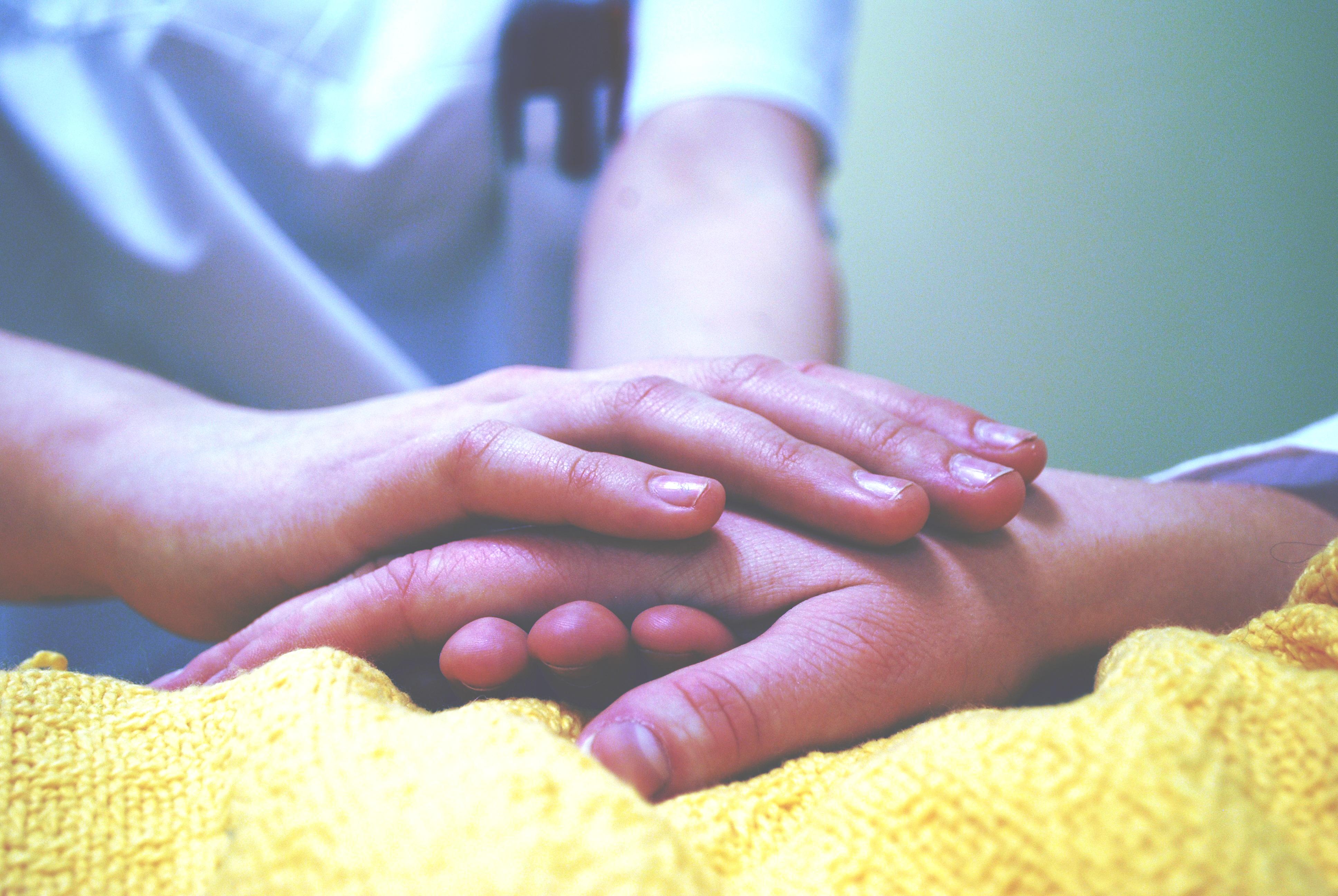 A nurse holding a patient's hand.